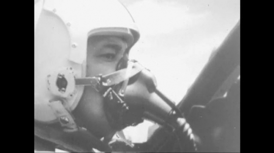 UNITED STATES: 1960s: pilot in mask in plane. Jet plane flies over coast and mountains