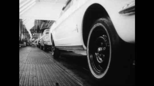 UNITED STATES: 1960s: cars on production line in factory. Man walks past car. Headlamps on car. Brake test on car