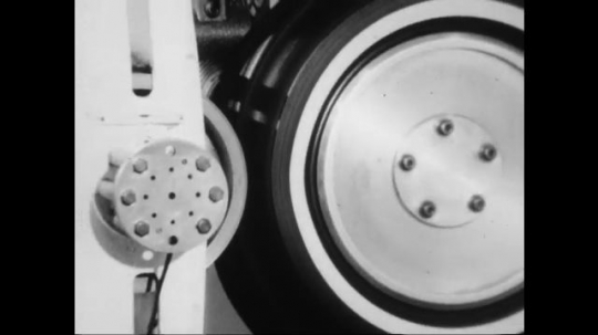 UNITED STATES: 1960s: wheel tested on machine by engineer. Men talk by wheel