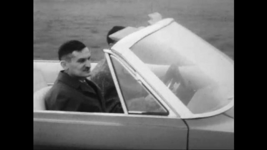 UNITED STATES: 1960s: two men test drive car on track. Close up of wheel