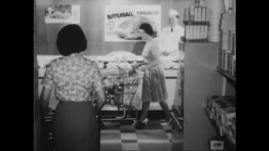 UNITED STATES: 1960s: ladies push carts in supermarket. Butterball poster on wall. Poultry counter in grocery store