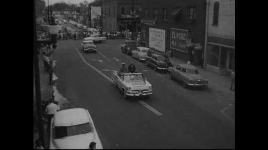 UNITED STATES: 1950s: cars drive through street. Marching band in procession.