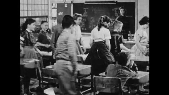 UNITED STATES: 1950s: students leave class. Boy sits at desk. Boy cleans chalk off blackboard. Boy draws cartoon on blackboard. Close up of boy