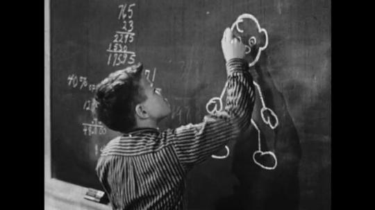 UNITED STATES: 1950s: Boy draws stickman on blackboard. Boy stares and thinks. Stickman talks to boy. Stickman walks, talks, and jumps on blackboard.