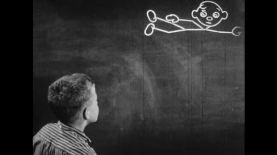 UNITED STATES: 1950s: Boy tries to rub out chalk drawing. Chalkboard animation talks to boy. Angry boy looks at blackboard.
