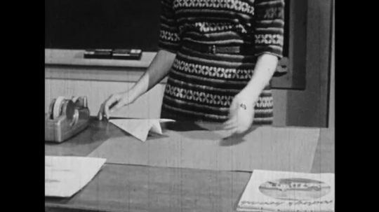 UNITED STATES: 1950s: Paper airplane lands on teacher's desk. Boy thinks and smiles. Boy talks to animation on blackboard. Teacher pins elephant picture on blackboard.