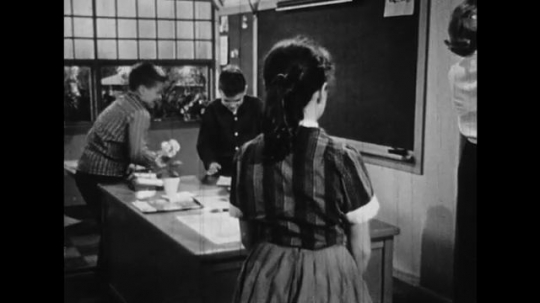 UNITED STATES: 1950s: Boys make fun of girl in class. Teacher sees boys being naughty in class. Girl upset in class.