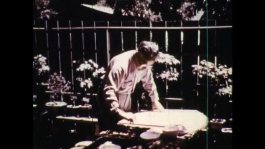 UNITED STATES: 1950s:  man works at table outdoors. Man paints in ink