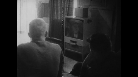 UNITED STATES: 1960S: people watch Kennedy on television set. Soldiers listen to speech.