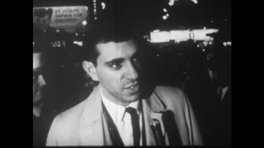 UNITED STATES: 1960S: man talks to camera. Lady interviewed by journalist.