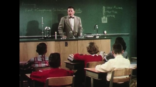 UNITED STATES: 1950s: science teacher lectures students. Boy speaks in class.