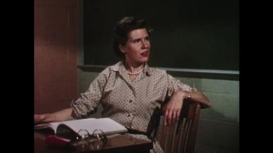 UNITED STATES: 1950s: teachers talk in classroom. Girl speaks to teacher.