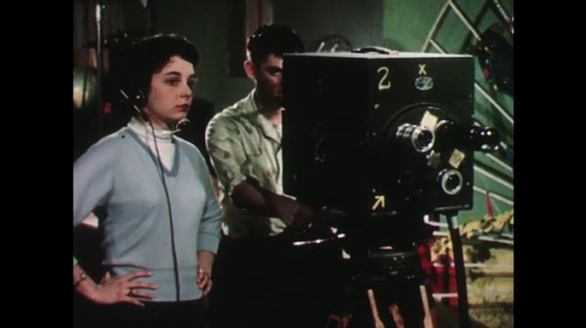 UNITED STATES: 1950s: lady stands by camera man. Lady directs broadcast. Man shows picture of tiger