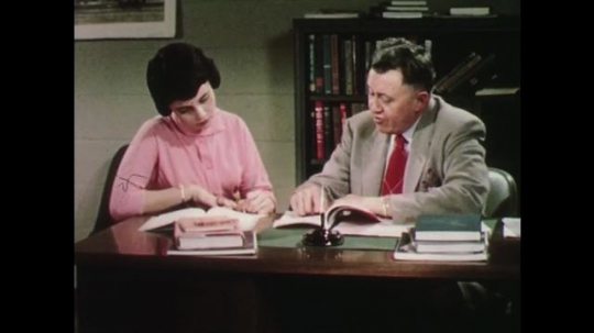 UNITED STATES: 1950s: girl talks to man at desk. Teacher helps student