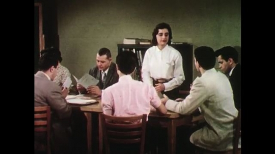 UNITED STATES: 1950s: men and women attend meeting in classroom. People leave meeting. Lady speaks to man.
