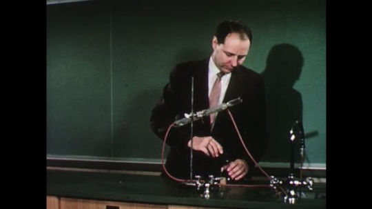 UNITED STATES: 1950s: teacher sets up science work in lab. New teacher arrives in class. Teacher shakes man