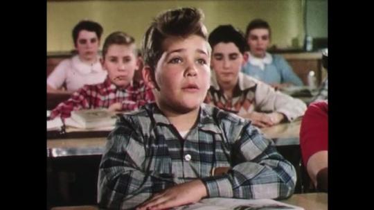UNITED STATES: 1950s: boy talks to teacher. Teacher blows into test tubes in rack.