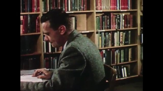 UNITED STATES: 1950s: man sits in library. Boy bangs with hammer. Student reads to teacher at desk