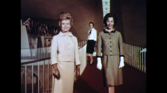 UNITED STATES: 1960s: ladies model clothes in building. Lady turns for camera.