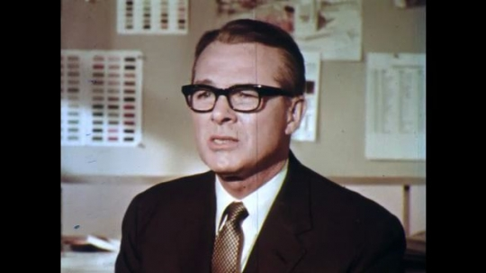 UNITED STATES: 1960s: man in glasses talks to camera. Lady interviews man.