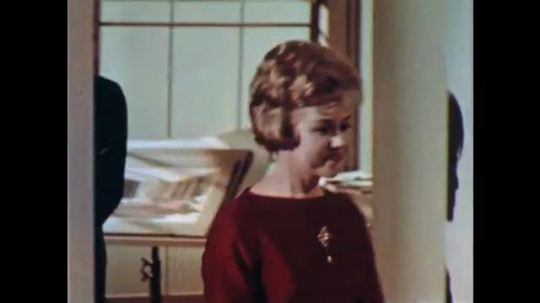 UNITED STATES: 1960s: lady walks into room. Man follows lady into room. View of room.