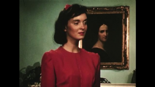 UNITED STATES: 1940s: lady looks at self in mirrors. Pattern for dress.