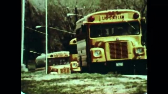 UNITED STATES: 1970s: school bus drives along road. Children run into school