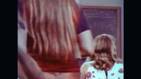 UNITED STATES: 1970s: students in class. Teachers in class. Girls talk in classroom. Students talk by lockers. Boy talks to girl