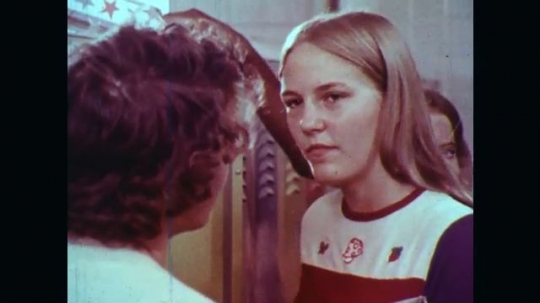 UNITED STATES: 1970s: boy talks to girl by school lockers. Students talk in corridor.