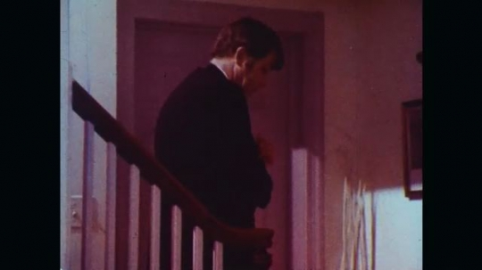 UNITED STATES: 1970s: man walks down stairs in suit. Man kisses girl on head. Parents leave girl for evening