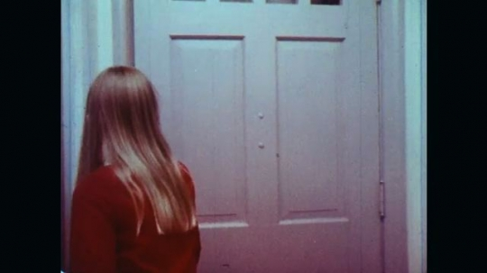 UNITED STATES: 1970s: girl answers door to friends. Teenagers in room.