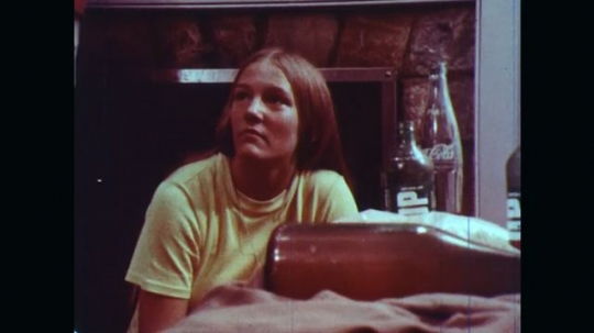 UNITED STATES: 1970s: girl looks worried. Girl drinks bottle of alcohol. Boy drinks from bottle