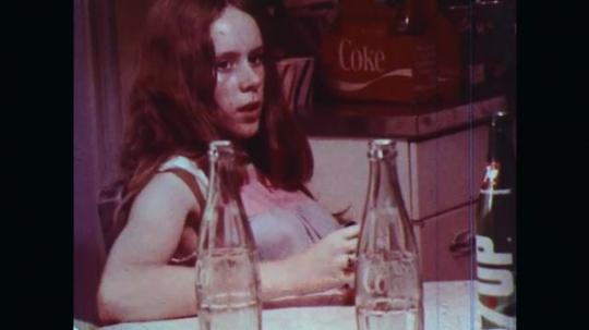 UNITED STATES: 1970s: girls talk in kitchen. Girl looks worried.