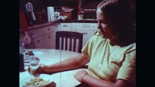 UNITED STATES: 1970s: girl sits in kitchen. Girls talk in kitchen. Girl eats snacks.