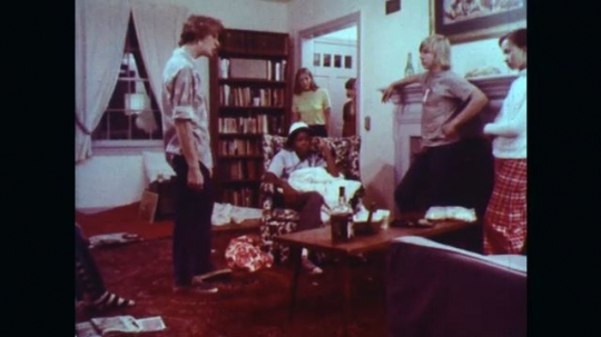 UNITED STATES: 1970s: girls see drunk boy. Boy gets angry and breaks table