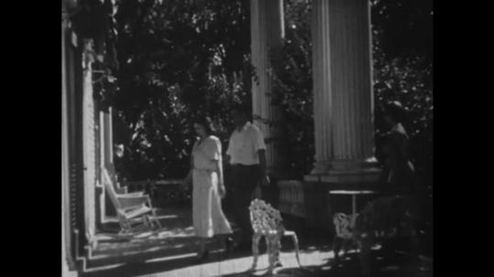 UNITED STATES: 1950s: family walk towards door. Gentleman opens door for family. Interior of building