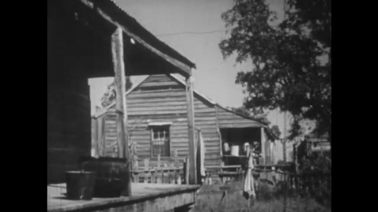 UNITED STATES: 1950s: side and front view of wooden buildings. Cart by building. Man works by fire.