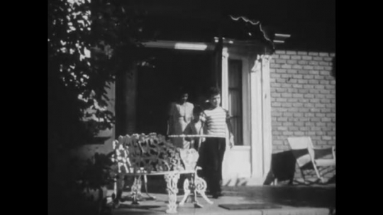 UNITED STATES: 1950s: family exit building. Family walk to car. Man opens car door for lady