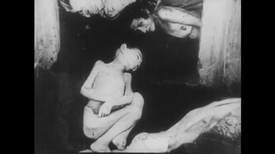 POLAND: 1960s: bodies of prisoners in camp. Naked boy and woman in camp. Concrete foundations of camp. Men shake hands