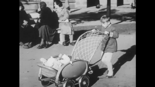 POLAND: 1960s: child pushes pram. Lady adjusts cover on pram. Baby in street. Building and road