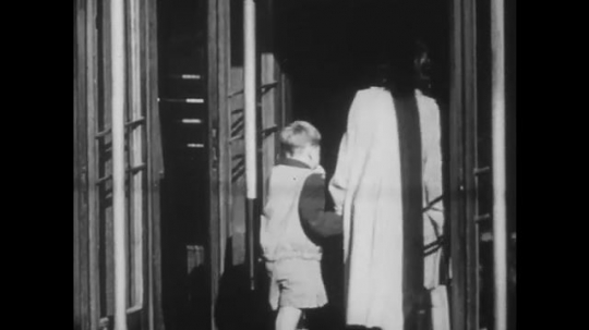 POLAND: 1960s: boy holds lady's hand. Lady and child enter building. Soldier leaves building. People walk in street