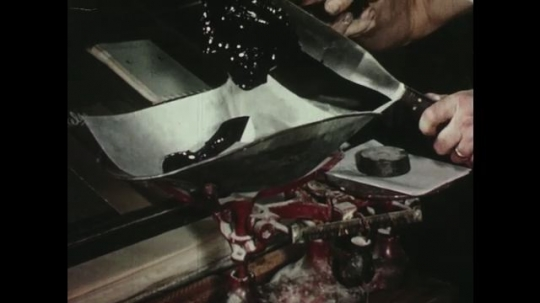UNITED STATES: 1950s: hands paste liquid onto table. Man prepares press.