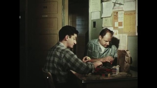 UNITED STATES: 1950s: men eat food and sort printing letters at table. Man wipes nose.