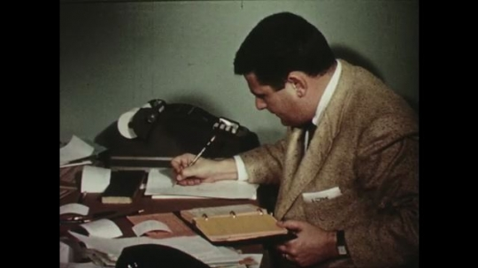 UNITED STATES: 1950s:  Man writes notes in book