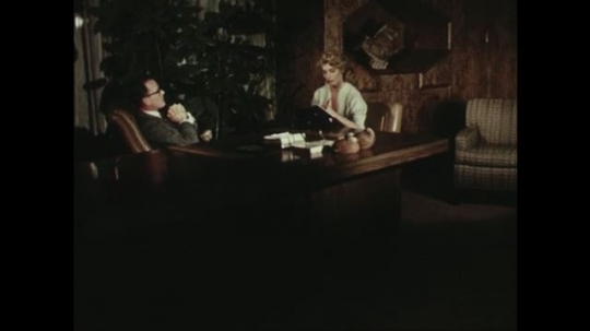 UNITED STATES: 1950s: Man and lady at office desk. Man wakes from nap and makes call.