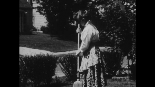 1950s: UNITED STATES: lady sweeps in street. Boy talks to lady. Dog runs across garden. Soap and water in sink. Lady talks to policeman.