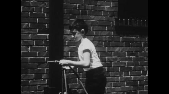 1950s: UNITED STATES: boy turns on hose. Boy in street.