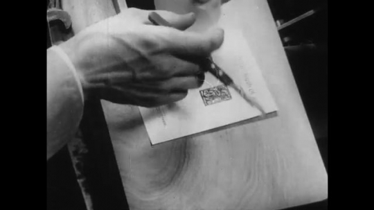 1950s: UNITED STATES: ands place tissue over printed impression. Hand cuts paper with knife.