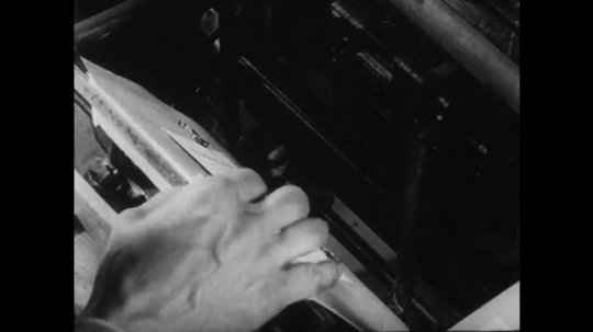 1950s: UNITED STATES: hand operates machine. Man removes packing from press.
