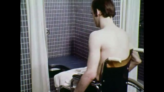 UNITED STATES: 1970s: man wheels chair into shower cubicle. Man puts soap on rope around neck. Man moves towels